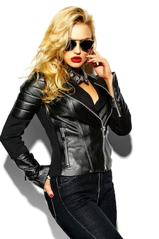 Piękna blondynka model ze skórzaną kurtką i okularami przeciwsłonecznymi