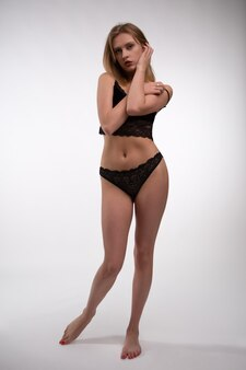 Piękna blondynka modelka w czarnej koronkowej bieliźnie pozowanie na białej ścianie.