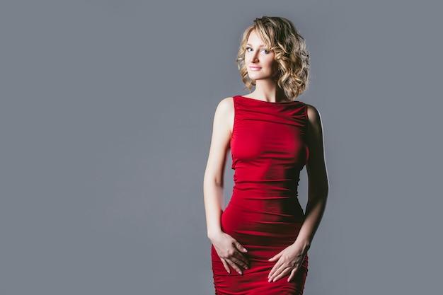Piękna blondynka modelka w czerwonej sukience modnej i eleganckiej w studio