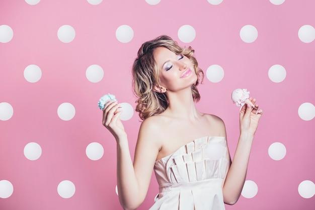 Piękna blondynka modelka z lodami i makijaż moda na różowym tle w studio