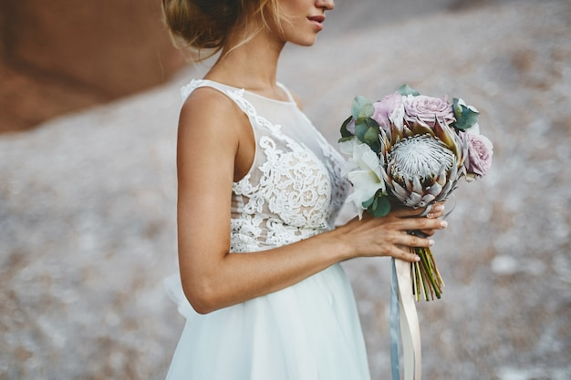 Piękna blondynka modelka z modelującą fryzurę ślubną w modnej białej koronkowej sukni z bukietem egzotycznych kwiatów w dłoniach