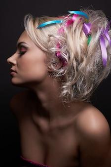 Piękna blondynka modelka z modnym jasnym makijażem iz kolorowymi wstążkami w jej stylową fryzurę, na białym tle na czarnym tle.