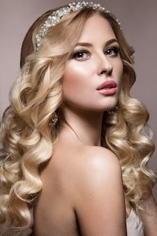 Piękna blondynka na ślubnym zdjęciu z lokami, jasnymi ustami i tiarą