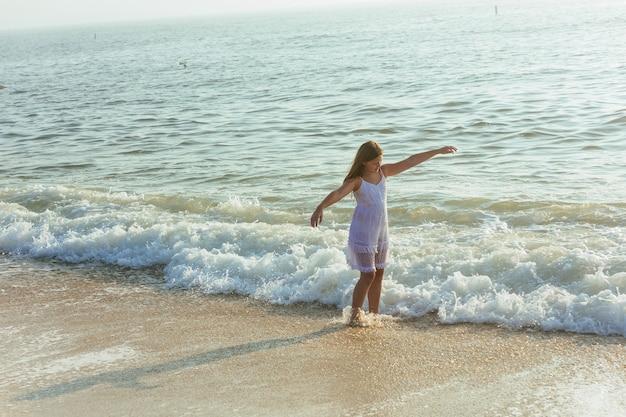 Piękna blondynka nastolatka ubrana w zwiewną białą sukienkę stojąca za kostkę w wodzie oceanu