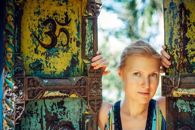 Piękna blondynka otwierająca drzwi zabytkowej bramy. portret młodej kobiety w autentycznym stylu przed półotwartymi starymi bramami. pojęcie odkrycia, nowe życie, przygoda. symbol om na drzwiach.