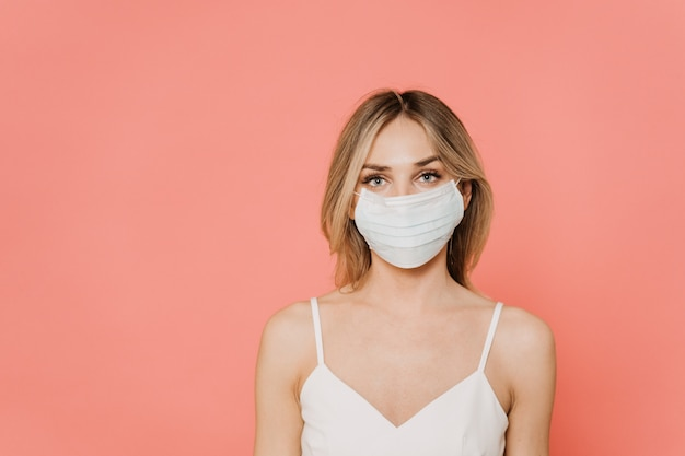 Piękna blondynka patrzeje ufny w chirurgicznie masce ochronnej, czekanie końcówka pandemia koronawirusa w domu, stoi nad różowym tłem z kopii przestrzenią. pojęcie opieki zdrowotnej.
