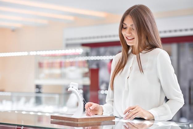 Piękna blondynka patrzy na naszyjnik w sklepie jubilerskim i uśmiecha się do siebie
