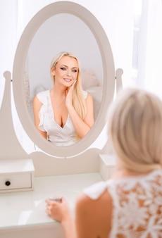 Piękna blondynka patrzy w lustro i nakłada krem na twarz.