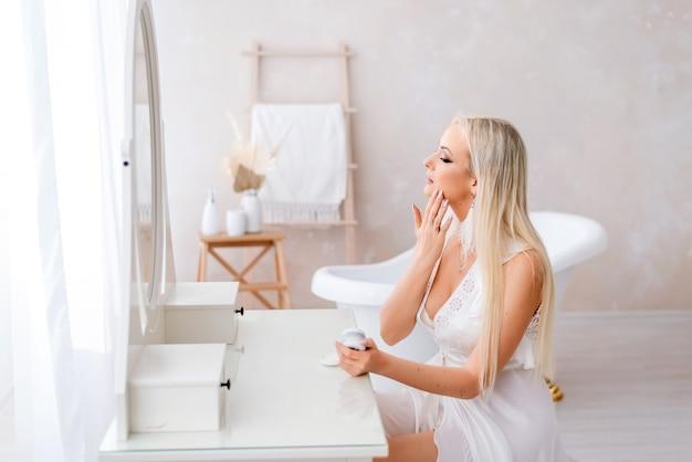 Piękna blondynka patrzy w lustro podczas stosowania kremu do twarzy
