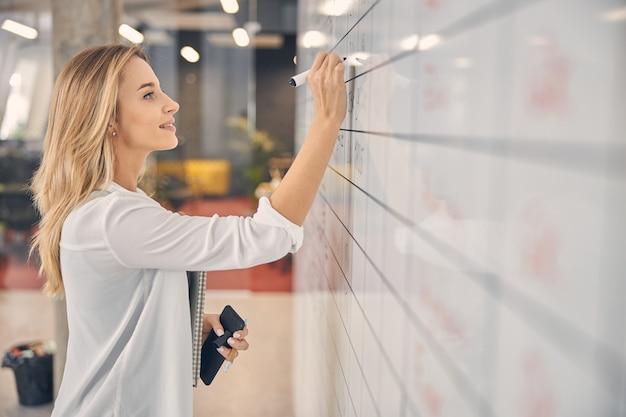 Piękna blondynka, pisząca na tablicy plannera i uśmiechająca się, trzymając smartfon