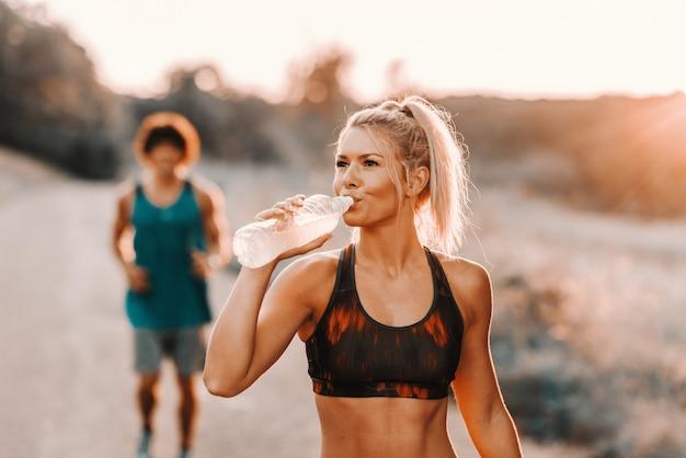 Piękna blondynka rasy białej wody pitnej, podczas gdy jej chłopak biegnie za nią.