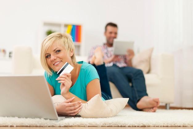 Piękna blondynka relaksuje w domu z laptopem i kartą kredytową