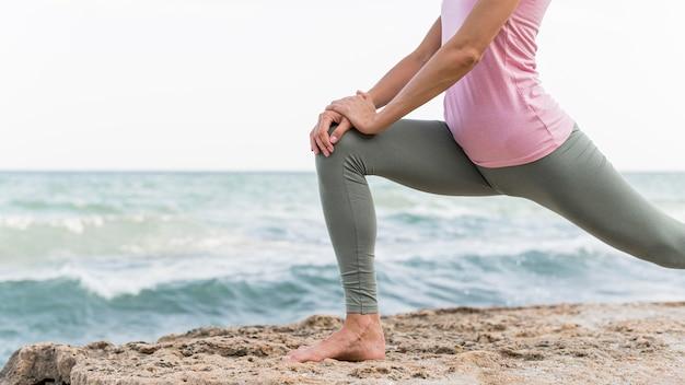 Piękna blondynka robi joga na plaży