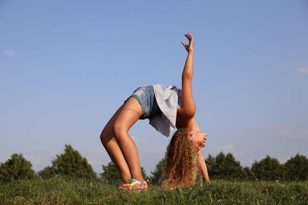 Piękna blondynka robi most gimnastyczny w przyrodzie. zdjęcie wysokiej jakości