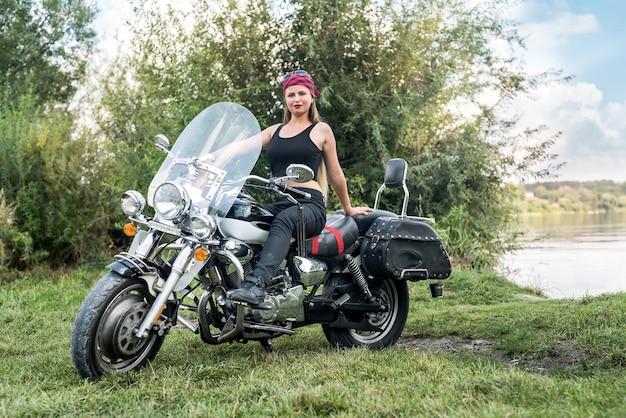 Piękna blondynka siedzi na motocyklu