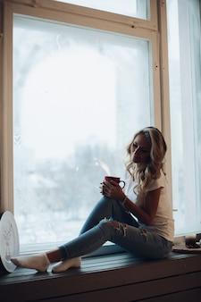 Piękna blondynka siedzi na parapecie z kubkiem