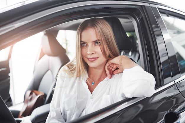 Piękna blondynka siedzi w nowym samochodzie z nowoczesnym czarnym wnętrzem