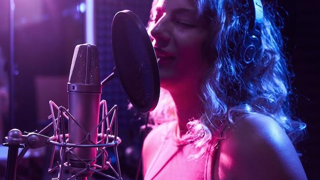 Piękna blondynka śpiewa emocjonalnie piosenkę w studiu nagraniowym z profesjonalnym mikrofonem i słuchawkami, tworzy nowy album z utworami, wokalista w różowym niebieskim świetle neonowym, twarz z bliska