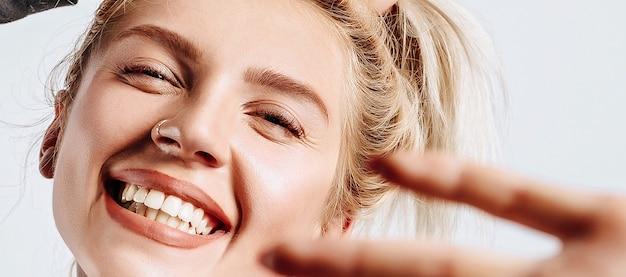 Piękna blondynka trzyma się za włosy i tworzy własną fryzurę z uczuciem szczęścia.