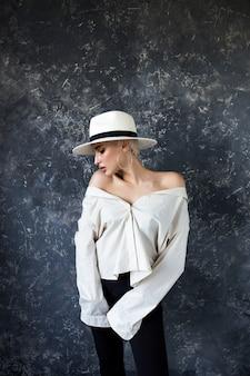 Piękna blondynka w białej koszuli i czarnych spodniach