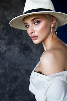 Piękna blondynka w białej koszuli z czarnymi spodniami i białym kapeluszu w studio na niebieskim tle