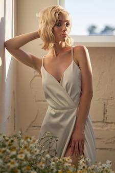 Piękna blondynka w białej sukni stoi przy oknie w wieczornym słońcu