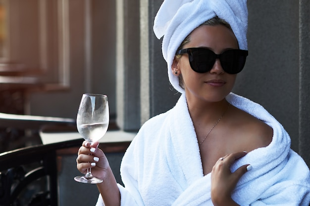 Piękna blondynka w białym płaszczu i okularach przeciwsłonecznych delektuje się lampką szampana