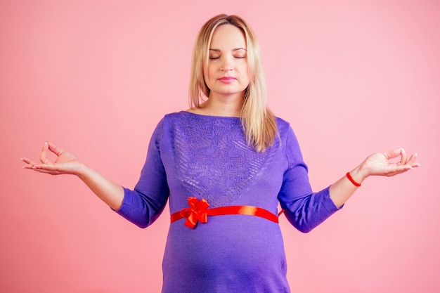 Piękna blondynka w ciąży w sukience z czerwoną satynową kokardką na brzuchu (baby bump) praktyka jogi i medytować w studio na różowym tle copyspace.
