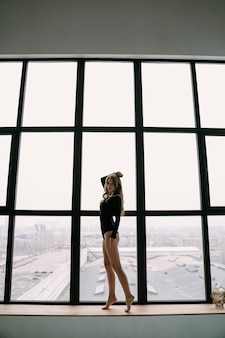Piękna blondynka w czarnym body w pobliżu dużego okna