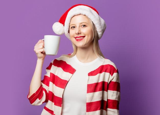Piękna blondynka w czerwonej kurtce i świątecznym kapeluszu na fioletowym tle
