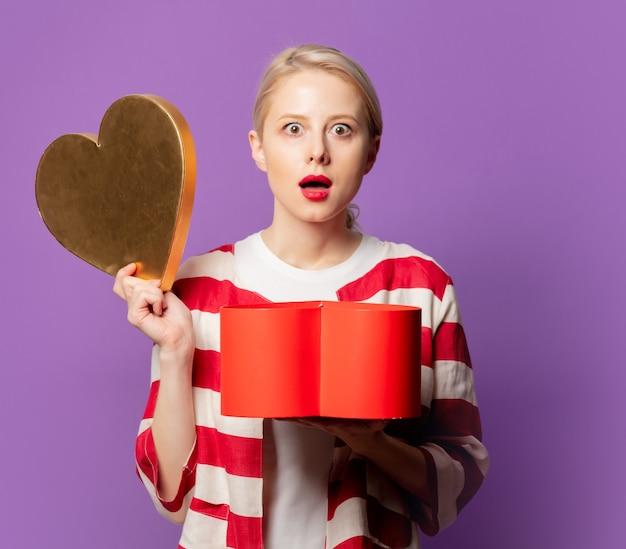 Piękna blondynka w czerwonej kurtce z pudełkiem w kształcie serca na fioletowym tle
