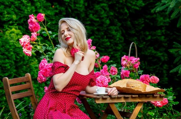 Piękna blondynka w czerwonej sukience picia kawy w ogrodzie