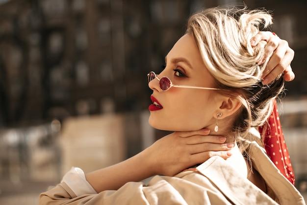 Piękna blondynka w czerwonych okularach przeciwsłonecznych dotyka włosów. elegancka dama w beżowym modnym trenczu pozuje na zewnątrz