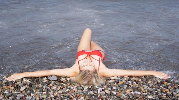 Piękna blondynka w czerwonym stroju kąpielowym opala się na kamienistej plaży w pobliżu morza. lubi słońce. leży z wyciągniętymi ramionami