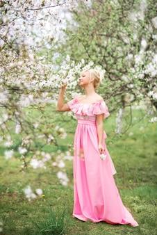 Piękna blondynka w długiej różowej sukience chodzi po wiosennym kwitnącym ogrodzie.