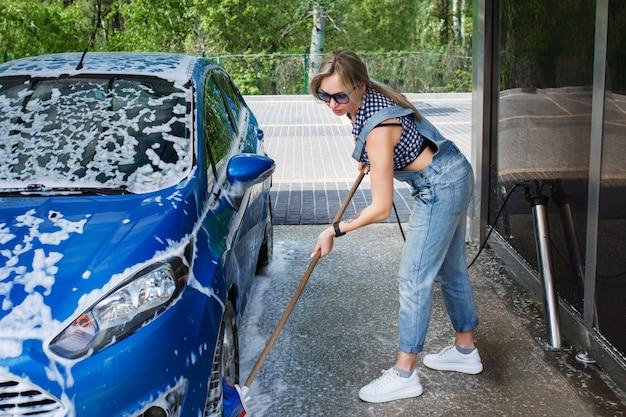 Piękna blondynka w dżinsowych kombinezonach myje samochód