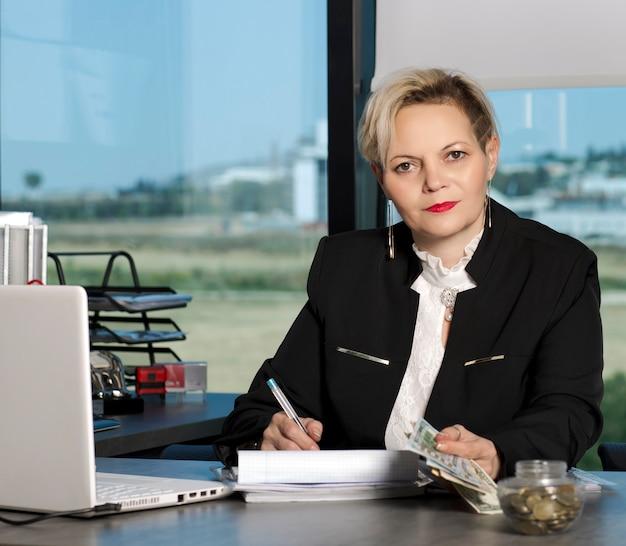 Piękna blondynka w garniturze, uśmiecha się do biurka za laptopem i papierami w biurze