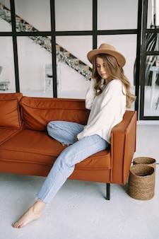 Piękna blondynka w kapeluszu siedzi na brązowej kanapie