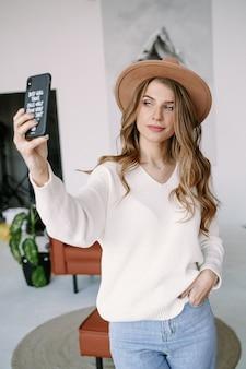 Piękna blondynka w kapeluszu sprawia, że selfie