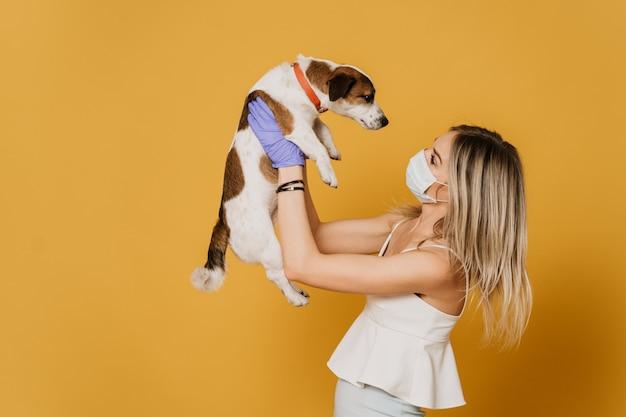 Piękna blondynka w masce chirurgicznej i rękawicach ochronnych, ubrana w lekką bluzkę i spódnicę, trzymająca swojego psa i patrząca na niego, podczas kwarantanny z powodu pandemii koronawirusa. koncepcja covid-19.