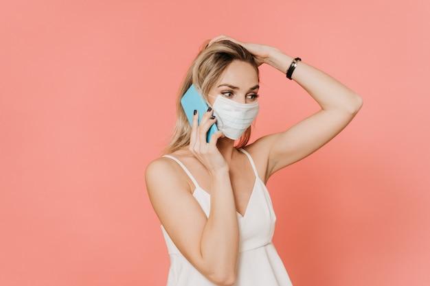 Piękna blondynka w masce chirurgicznej rozmawiająca przez telefon ze swoimi starszymi rodzicami martwi się o ich stan z powodu wywołania pandemii koronawirusa. na różowym tle. pojęcie opieki zdrowotnej.