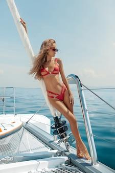 Piękna blondynka w morzu otwartym na jachcie na sobie czerwone bikini
