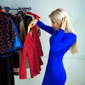 Piękna blondynka w niebieskiej sukience wybiera koszulę w sklepie odzieżowym