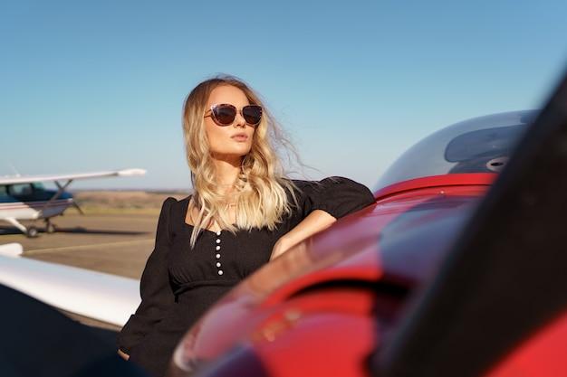 Piękna blondynka w nowoczesnych okularach przeciwsłonecznych pozuje w pobliżu czerwonego prywatnego samolotu z niebem