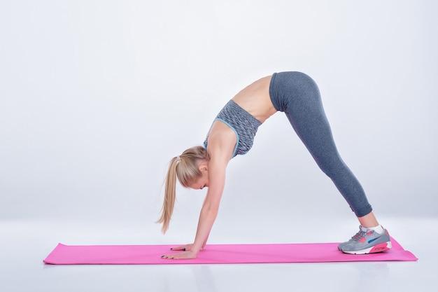 Piękna blondynka w odzieży sportowej robi ćwiczenia na matę fitness na szarym tle. kobieta ćwicząca jogę