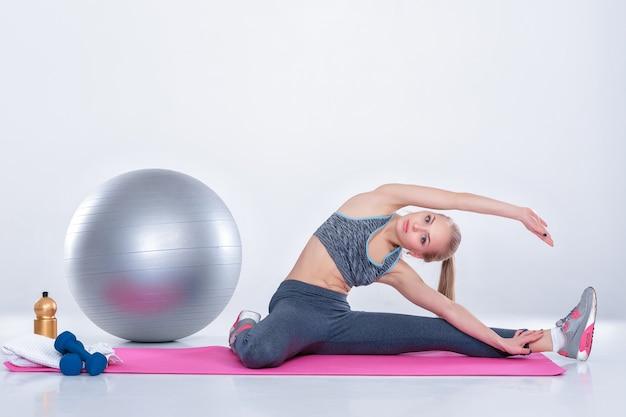 Piękna blondynka w odzieży sportowej robi ćwiczenia na matę fitness na szarym tle. rozciąganie
