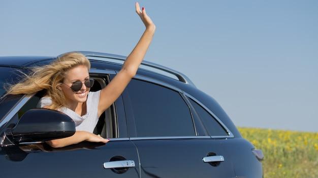 Piękna blondynka w okularach przeciwsłonecznych wychyla się i macha z okna samochodu
