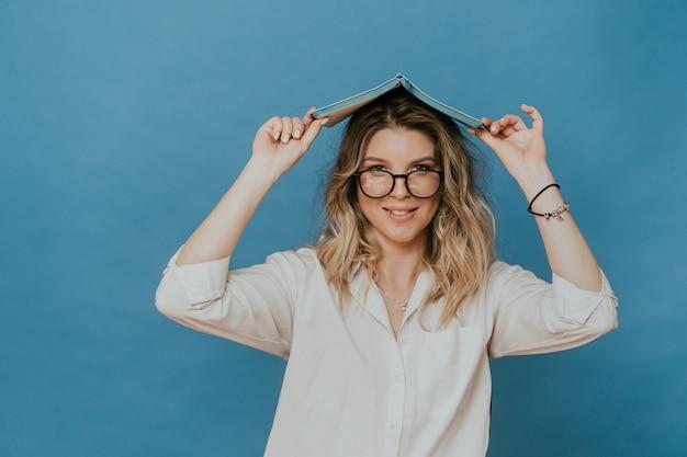 Piękna blondynka w okularach, ubrana w białą koszulę, tworzy dziennik dach pod głową, pracując w domu z powodu izolacji. zostań w domu podczas kwarantanny. koncepcja covid-19.