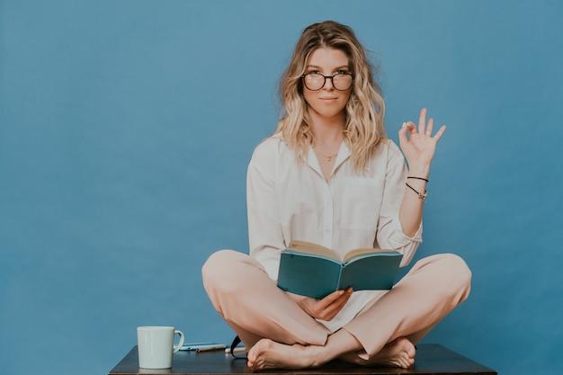 Piękna blondynka w okularach, ubrana w lekkie ubranie, siedząca na stole, trzymająca swój pamiętnik i gestykulujący znak ok inną ręką, zostaje w domu podczas pandemii koronawirusa. koncepcja cove-19.