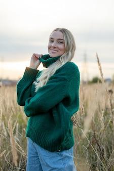 Piękna blondynka w polu pszenicy o zachodzie słońca stoi i patrzy w kamerę.